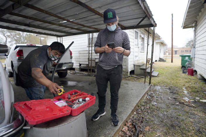 Ben Hirsch, with West Street Recovery, checks his phone as Martin Uribe reaches for tools while repairing busted pipes at a home, Thursday, Feb. 25, 2021, in Houston. West Street Recovery, a nonprofit created in the wake of Hurricane Harvey to help repair flood damaged homes, has been working since the winter storm hit to repair and replace damaged plumbing systems for residents who can't afford to do so. (AP Photo/David J. Phillip)