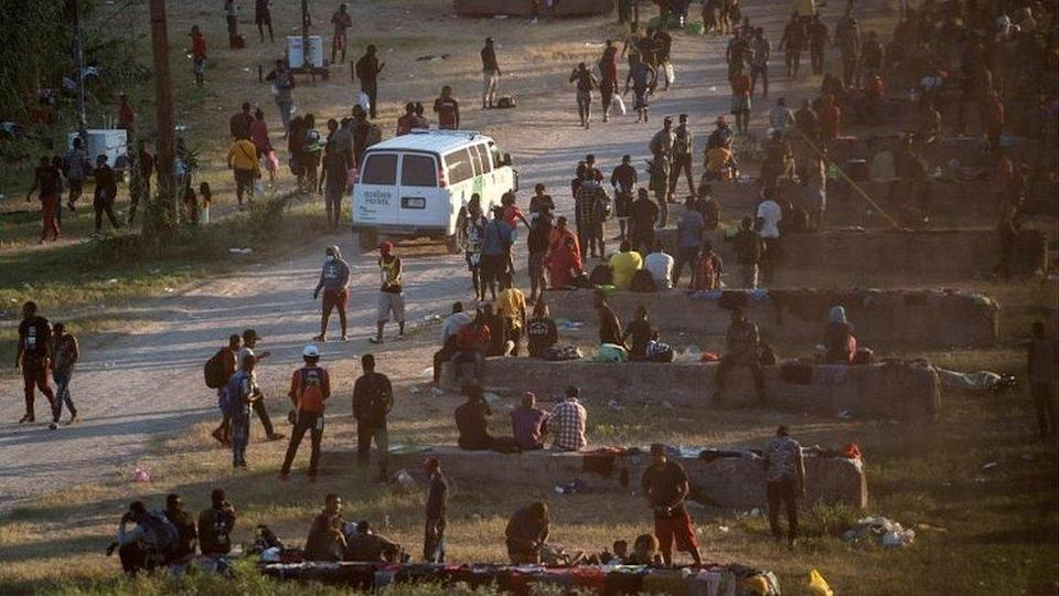 Migrants seeking asylum in the US rest near the International Bridge between Mexico and the US as they wait to be processed, in Del Rio, Texas, on 16 September 2021
