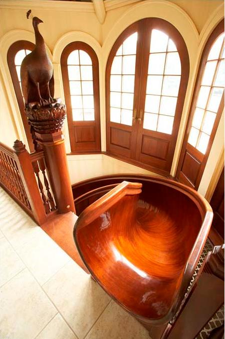 """My 28-foot wooden circular mahogany slide took more than 15 months to  build. The slide was formed with a cold-molding technique that used two  kinds of mahogany, 30 gallons of epoxy, and 40,000 staples, 36,000 of  which were removed after the epoxy dried. Once the slide was installed  in my home, spiraling stairs were built around it so that they were  ""married"" to its curvature,"" explains inventor Scott A. Jones.<br><br>(Photo courtesy of <a target=""_blank"" href=""http://www.scottajones.com/"">Scott A. Jones</a>)"