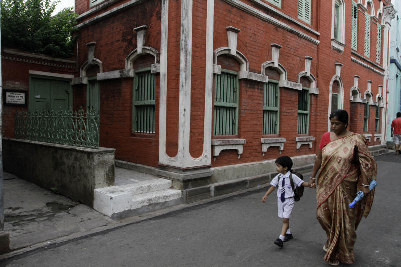 """A woman and a child walk past the the No. 22, Iswar Mil Lane house where Indian scientist Satyendranath Bose, lived in Kolkata, India, Tuesday, July 10, 2012. While much of the world was celebrating the international cooperation that led to last week's breakthrough in identifying the existence of the Higgs boson particle, many in India were smarting over what they saw as a slight against one of their greatest scientists. Media covering the story gave lots of credit to British physicist Peter Higgs for theorizing the elusive subatomic """"God particle,"""" but little was said about Satyendranath Bose, the Indian after whom the boson is named. (AP Photo/Bikas Das)"""