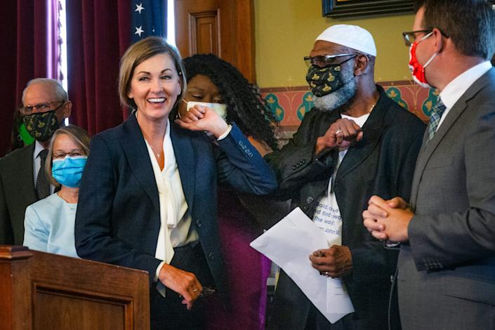 Gov. Kim Reynolds and state Rep. Ako Abdul-Samad bump elbows after the governor's signing of Executive Order 7, which restores the right to vote for Iowans who have completed felony sentences. Iowa had been the last state to permanently prohibit convicted felons from voting.