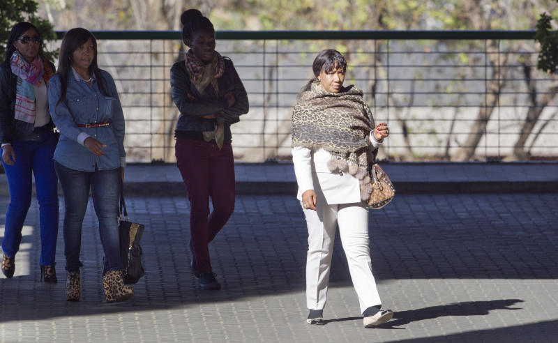 Granddaughter Tukwini Mandela, left, granddaughter Ndileka Mandela, second left, and daughter Makaziwe Mandela, right, arrive at the Mediclinic Heart Hospital where former South African President Nelson Mandela is being treated in Pretoria, South Africa Friday, June 28, 2013. One of the former president's daughters said he is still opening his eyes and reacting to the touch of his family even though his situation is precarious. Woman at second right is unidentified. (AP Photo/Ben Curtis)