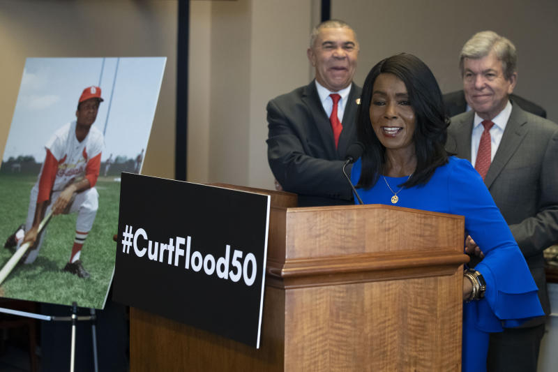 Rep. William Lacy Clay, D-Mo., left, and Sen. Roy Blunt, R-Mo., right, stand as Judy Pace Flood speaks during a news conference as they call for the late Curt Flood to be inducted into the Baseball Hall of Fame, on Capitol Hill, Thursday, Feb. 27, 2020 in Washington. (AP Photo/Alex Brandon)