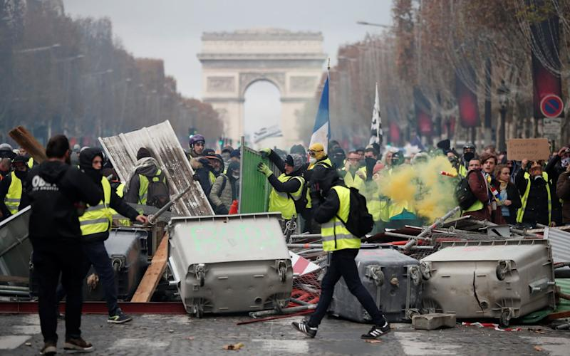 Protesters wearing yellow vests, build a barricade during clashes on the Champs-Elysees in Paris on Saturday November 24 - REUTERS