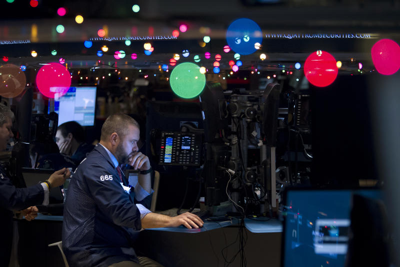 Trader Kevin Lodewick works on the floor of the New York Stock Exchange, which has been decorated with Christmas lights, in New York December 22, 2014. REUTERS/Carlo Allegri (UNITED STATES - Tags: BUSINESS)