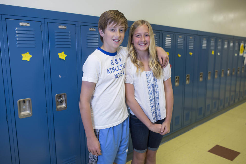 In this Thursday, June 6, 2013 photo, Mason Mackenzie, left, and his twin sister, Greer, one of the 24 sets of twins from Highcrest Middle School in Wilmette, Ill. pose for a portrait at the school. The group is attempting to break a Guinness World record for the amount of twins in one grade which is currently 16 sets. (AP Photo/Scott Eisen)