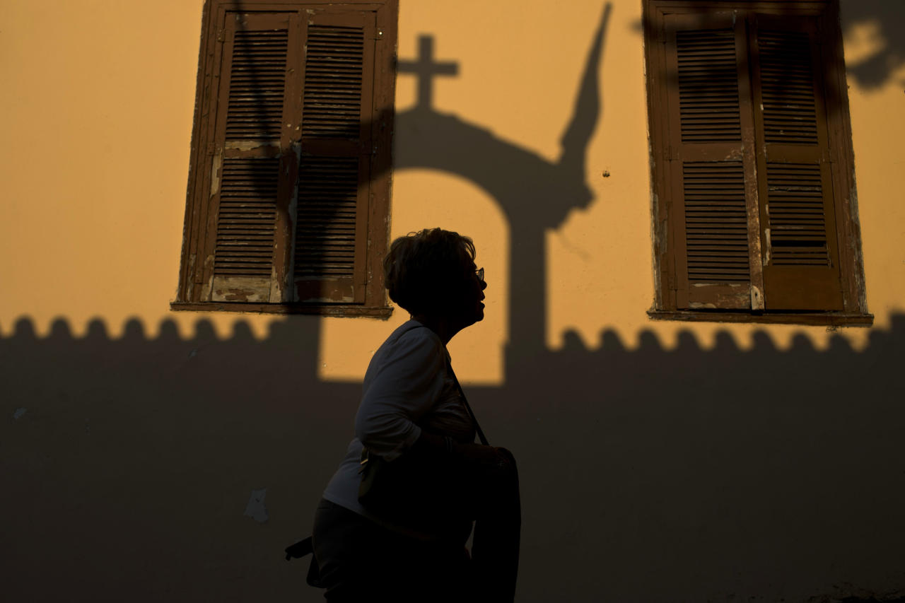 A woman walks in the Plaka district of Athens, as the shadow of a church is seen on a building, on Tuesday, May 22, 2017. Lying under the shadow of the ancient Acropolis Hill, Plaka's narrow streets and neoclassical architecture have for decades attracted tourists and Athenians alike.(AP Photo/Petros Giannakouris)