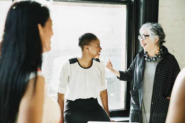 Senior businesswoman laughing with colleague during meeting in creative office