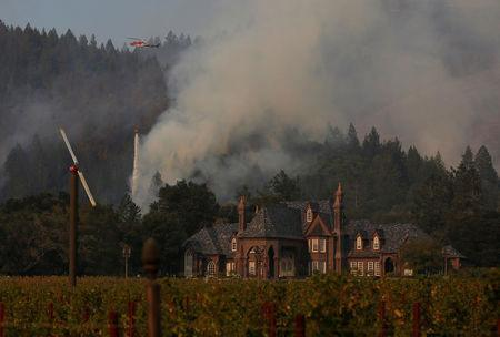 A firefighting helicopter drops water to defend a vineyard from an approaching wildfire in Santa Rosa, California, U.S., October 14, 2017. REUTERS/Jim Urquhart