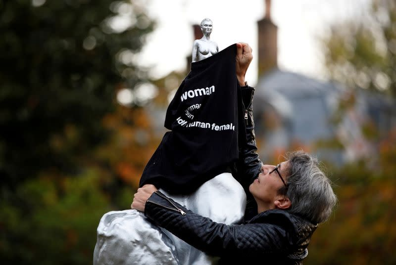 A protester covers with a t-shirt the Mary Wollstonecraft statue 'Mother of feminism' by artist Maggi Hambling in Newington Green, London