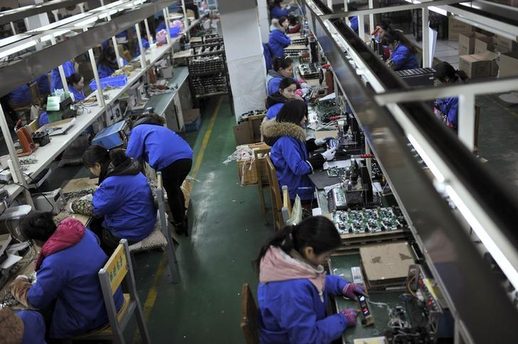 Employees assemble electronic components along a production line at a factory in Hefei