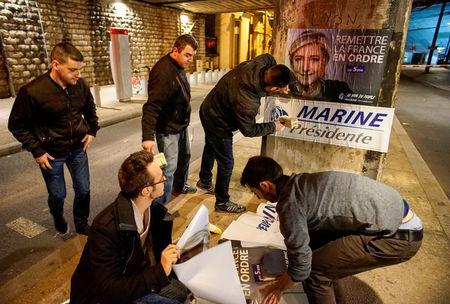 FILE PHOTO: Members of the National Front youths put up posters of Marine Le Pen, French National Front (FN) political party leader and candidate for the French 2017 presidential election, ahead of a 2-day FN political rally to launch the presidential campaign in Lyon, France, February 2, 2017. REUTERS/Robert Pratta/File photo/File Photo