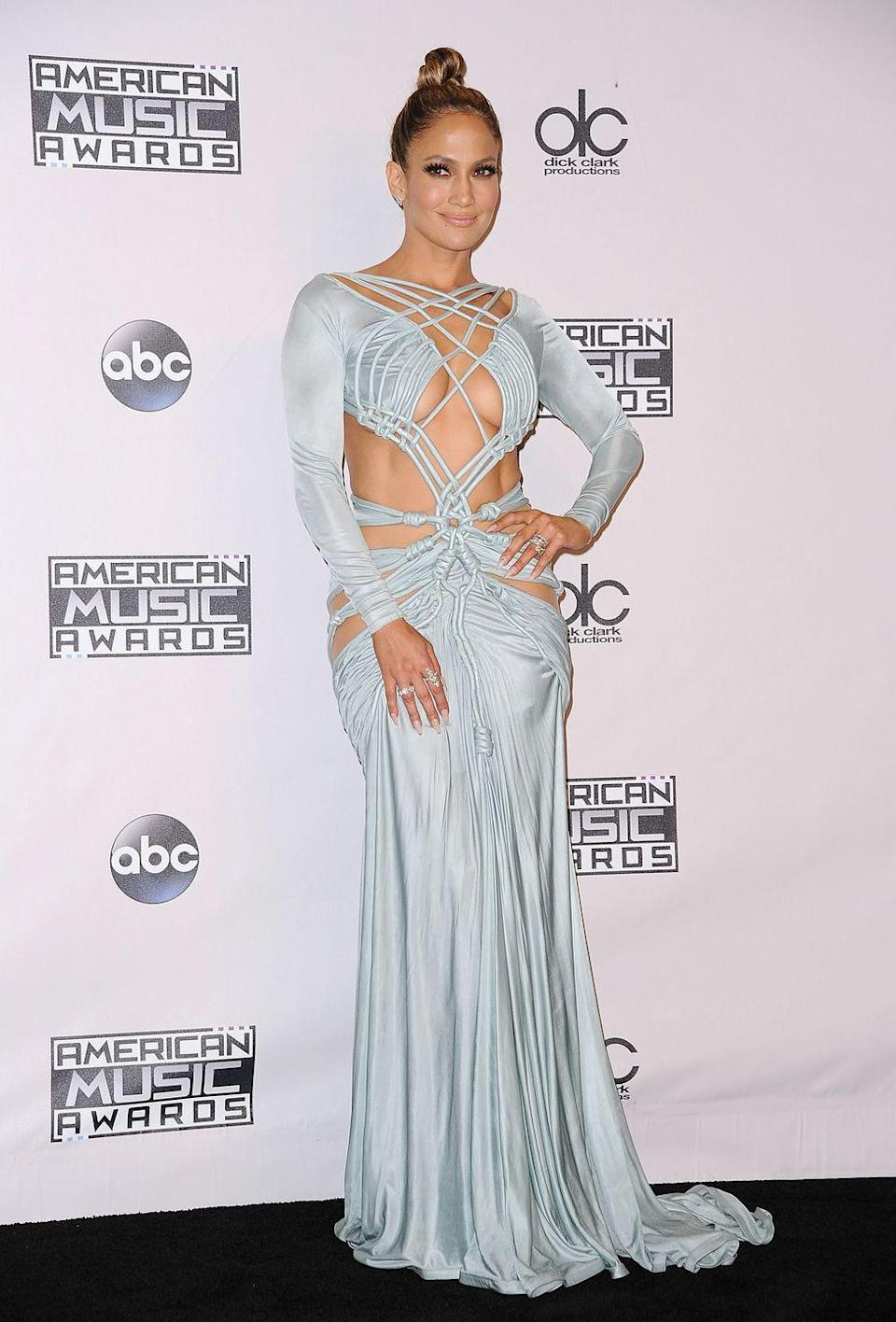 "<p>J.Lo attends the 2015 AMAs in this strappy blue gown, statement rings, and high bun. Also, let's not forget she lit-er-a-lly had <a href=""https://www.cosmopolitan.com/entertainment/celebs/news/a49700/jlo-2015-amas-outfits/"" rel=""nofollow noopener"" target=""_blank"" data-ylk=""slk:10 outfit changes"" class=""link rapid-noclick-resp"">10 outfit changes</a> that night, mmmkay? Your fave could never. </p>"