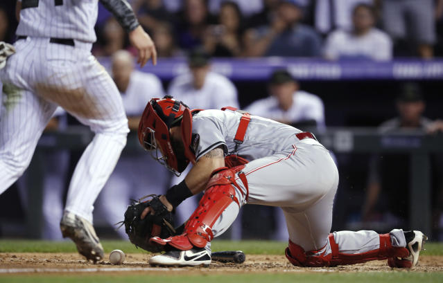 Cincinnati Reds catcher Tony Cruz, right, picks up the ball to force out Colorado Rockies' Ryan McMahon as he tries to score on a bases-loaded ground ball hit by Charlie Blackmon to Reds first baseman Joey Votto during the ninth inning of a baseball game Saturday, May 26, 2018, in Denver. The Reds won 6-5. (AP Photo/David Zalubowski)