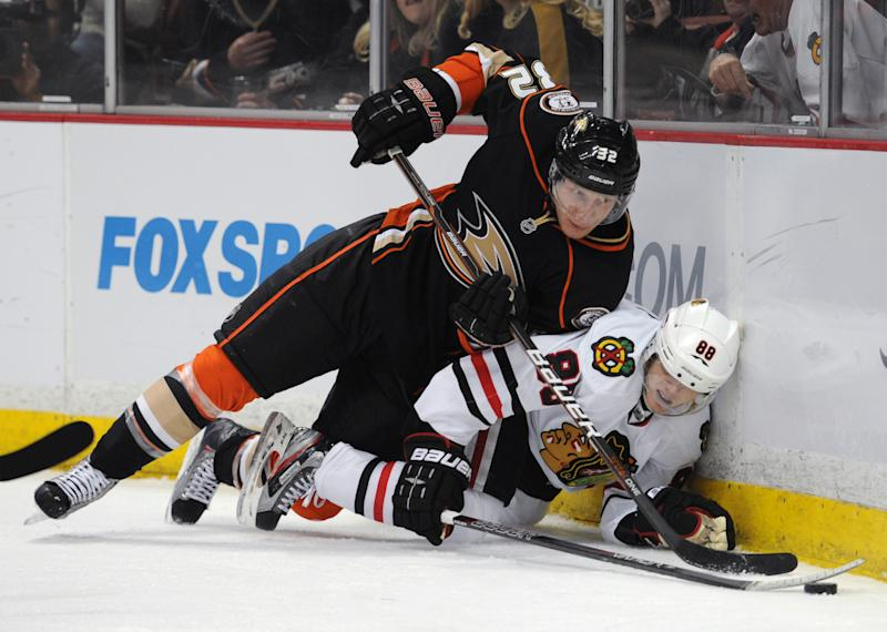 Chicago Blackhawks right wing Patrick Kane (88) and Anaheim Ducks defenseman Toni Lydman (32) fall to the ice during the first period of an NHL hockey game in Anaheim, Calif., Sunday, Feb. 26, 2012. (AP Photo/Lori Shepler)
