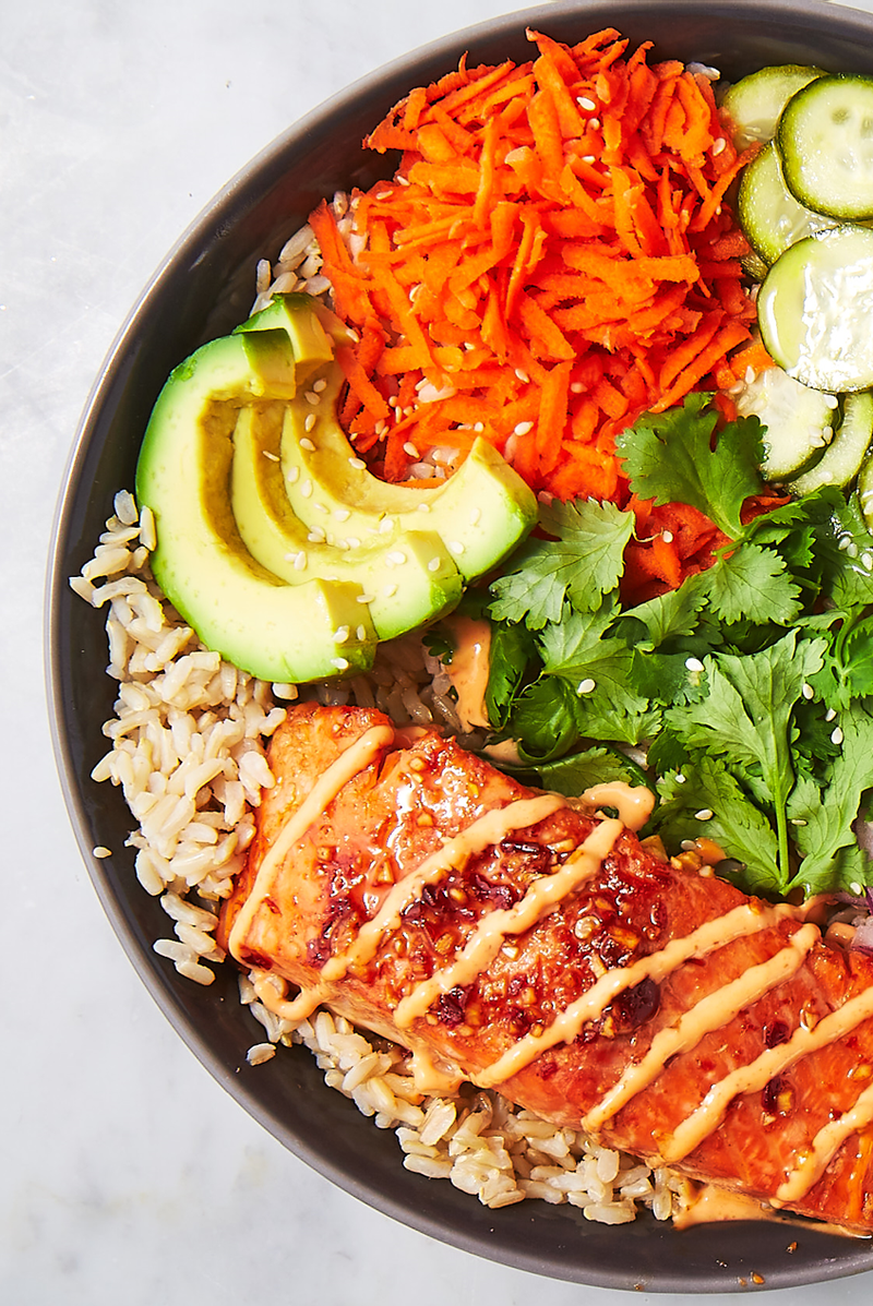 """<p>There is something magical about grain bowls. This spicy salmon bowl has all of our favourite things, and is by far our favourite bowl to date.</p><p>Get the <a href=""""https://www.delish.com/uk/cooking/recipes/a29843921/spicy-salmon-bowl-recipe/"""" rel=""""nofollow noopener"""" target=""""_blank"""" data-ylk=""""slk:Spicy Salmon Bowl"""" class=""""link rapid-noclick-resp"""">Spicy Salmon Bowl</a> recipe.</p>"""