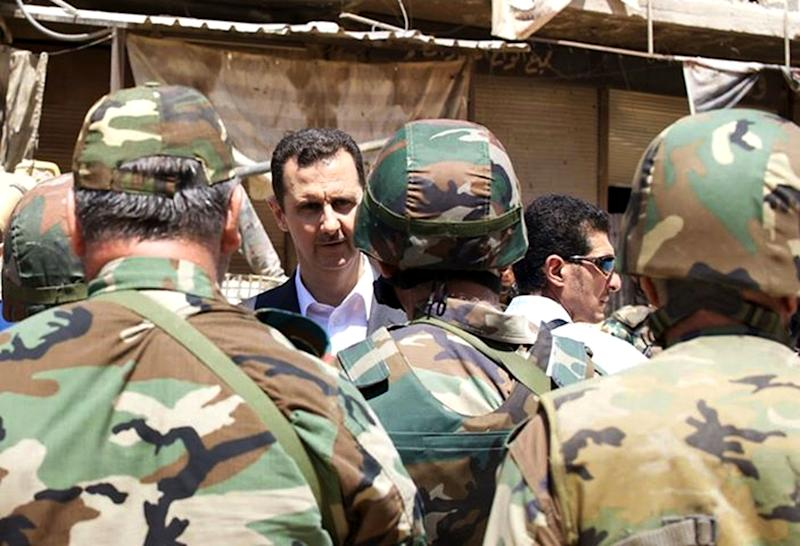 FILE - This Thursday, Aug.1, 2013 file photo posted on the official Facebook page of the Syrian Presidency, purports to show Syrian President Bashar Assad talking with soldiers with during Syrian Arab Army day in Darya, Syria. As the Obama administration tries to prod Congress into backing armed action against Syria, the regime in Damascus is hiding military hardware and shifting troops out of bases into civilian areas. (AP Photo/Syrian Presidency via Facebook, File)