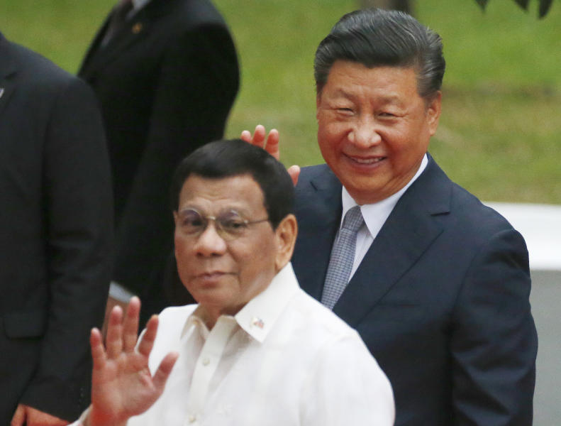 """FILE - In this Tuesday, Nov. 20, 2018, file photo, Chinese President Xi Jinping, right, and Philippine President Rodrigo Duterte wave to the media following a welcome ceremony at Malacanang Palace in Manila, Philippines. President Duterte says he has few options other than to order troops to """"prepare for suicide missions"""" if a Philippine-occupied island comes under threat from China. Duterte reminded China in a speech Thursday, April 4, 2019 of its closer ties with the Philippines under his leadership, but said if an island occupied by Filipinos in the disputed waters is threatened, """"things would be different.""""(AP Photo/Bullit Marquez, File)"""