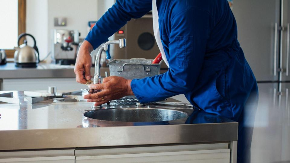 A shot of a man's hands working on a kitchen sink.