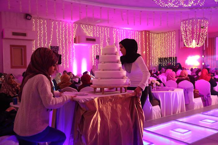 "Palestinian Sahar Yaghi, left, 28, prepares to serve cake at a wedding in Gaza City on Dec. 2, 2018. Yaghi took up work as a wedding planner soon after dropping out of university to earn income for her family. She said she sometimes hears some of her neighbors, who view her work as inappropriate, making comments about her. ""I hate some comments. But I love my job and hope to have my own business,"" Yaghi said. (Photo: Samar Abo Elouf/Reuters)"