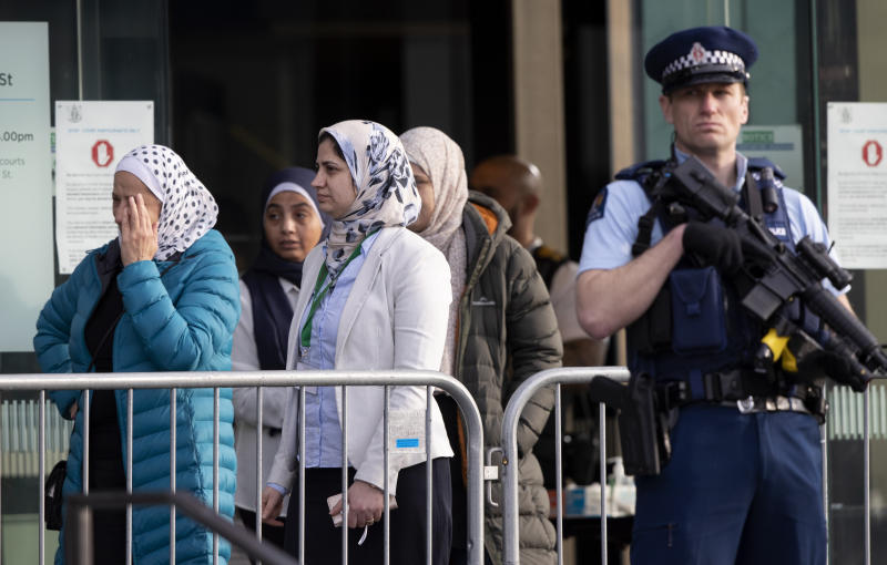 A group of women leave the Christchurch High Court as a police officer stands guard.