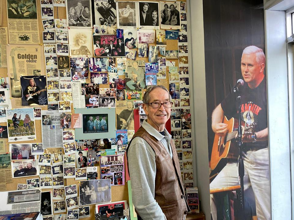 Music shop owner Tom Pickett stands in front of a life size photograph of Mike Pence in the doorway of his shop in Columbis, Indiana. Mr Pickett taught the former vice president how to play guitar when he was a senior in high school.  (Richard Hall / The Independent )