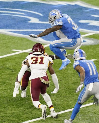 Detroit Lions running back D'Andre Swift (32) leaps over Washington Football Team safety Deshazor Everett (22) during the first half of an NFL football game Sunday, Nov. 15, 2020, in Detroit. (AP Photo/Carlos Osorio)