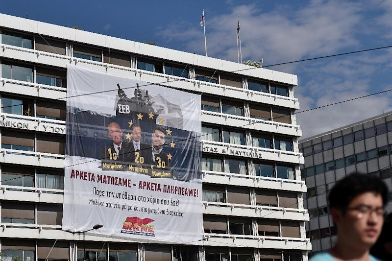 "A banner depicting former prime ministers George Papandreou, Antonis Samaras and current premier Alexis Tsipras and reading ""We have bled enough"" is hung by the communist-affiliated PAME union at the finance ministry in Athens on June 11, 2015 (AFP Photo/Louisa Gouliamaki)"