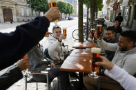 People toast with beers at a café terrace Wednesday, May, 19, 2021 in Strasbourg, eastern France. It's a grand day for the French. Café and restaurant terraces are reopening Wednesday after a shutdown of more than six months deprived people of what feels like the essence of life — sipping coffee and wine with friends outdoors — to save lives during the coronavirus pandemic. (AP Photo/Jean-Francois Badias)