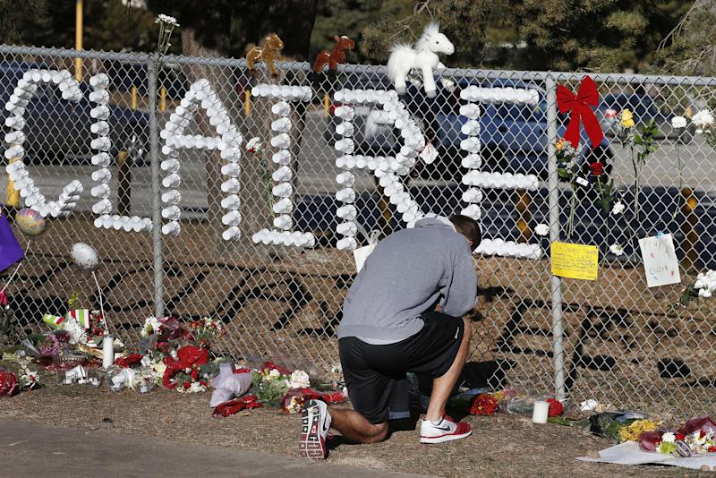 """Parker Semin, a 2011 Arapahoe High School graduate, prays at a makeshift memorial bearing the name of wounded student Claire Davis, who was shot by a classmate during school three days earlier in an attack, in front of Arapahoe High School in Centennial, Colo., Monday, Dec. 16, 2013. Semin said he came by to pray for the """"speedy recovery"""" of Davis, age 17, who was shot in the head at close range with a shotgun, and remains in a coma. (AP Photo/Brennan Linsley)"""