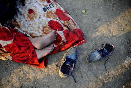 An immigrant, part of a new group of more than a thousand immigrants, sleeps as they wait at the border line of Macedonia and Greece to enter into Macedonia near Gevgelija railway station August 20, 2015. REUTERS/Ognen Teofilovski