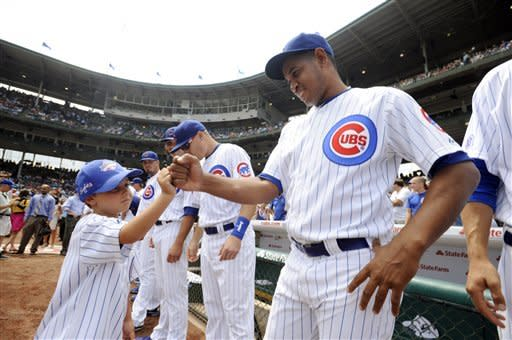 Hall of Fame player Ron Santo's grandson Spencer Brown, 7, fist pumps Chicago Cubs pitcher Carlos Marmol after throwing out the ceremonial first pitch before a baseball game between the Chicago Cubs and the St. Louis Cardinals during Ron Santo Day in Chicago, Friday, July 27, 2012. (AP Photo/Paul Beaty)