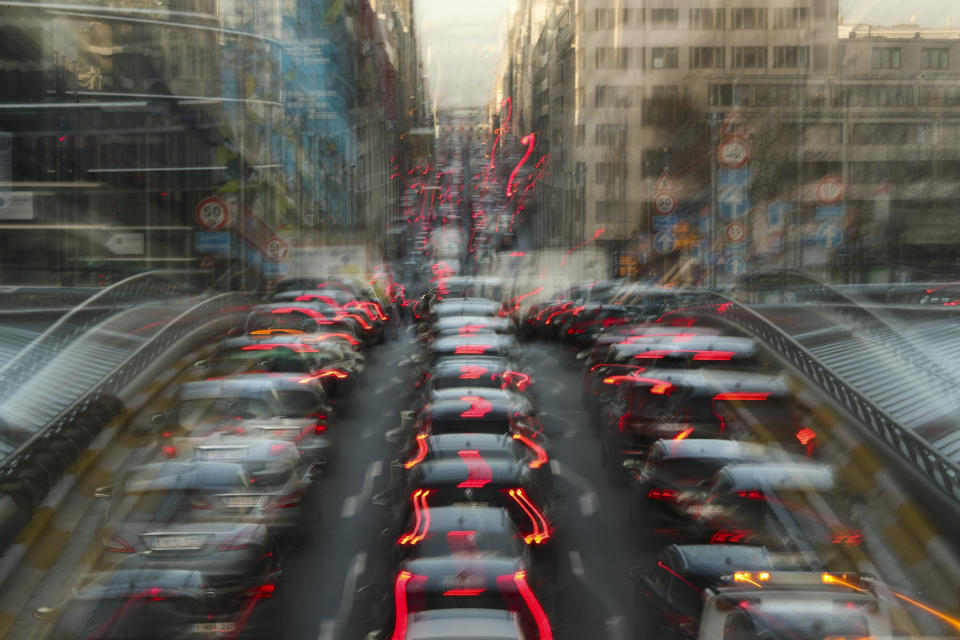 In this slow-shutter zoom effect photo, commuters backed up in traffic during the morning rush hour in Brussels, Tuesday, Dec. 10, 2019. The Belgium capital regularly experiences pollution alert warnings. (AP Photo/Francisco Seco)