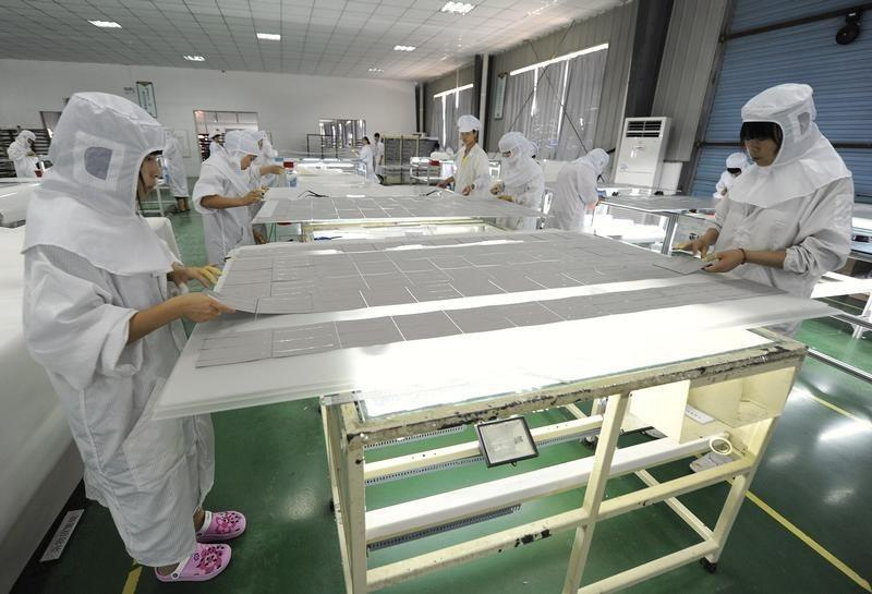 Employees process solar panel components at a solar power plant in Hefei