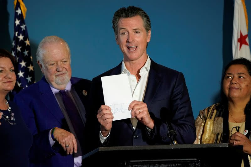 FILE PHOTO: California governor Gavin Newsom reacts after signing SB 113, which will enable the transfer of $331million in state funds to the National Mortgage Special Deposit Fund in San Diego, California