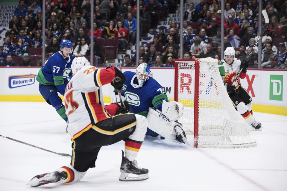 Calgary Flames' Sean Monahan, front, scores against Vancouver Canucks goalie Jacob Markstrom (25), of Sweden, as Canucks' Tyler Myers (57) and Flames' Johnny Gaudreau (13) watch during the third period of an NHL hockey game Saturday, Feb. 8, 2020, in Vancouver, British Columbia. (Darryl Dyck/The Canadian Press via AP)