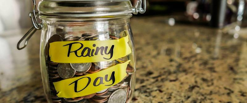 Rainy Day Money Jar. A clear glass jar filed with coins and bills, saving money. The words