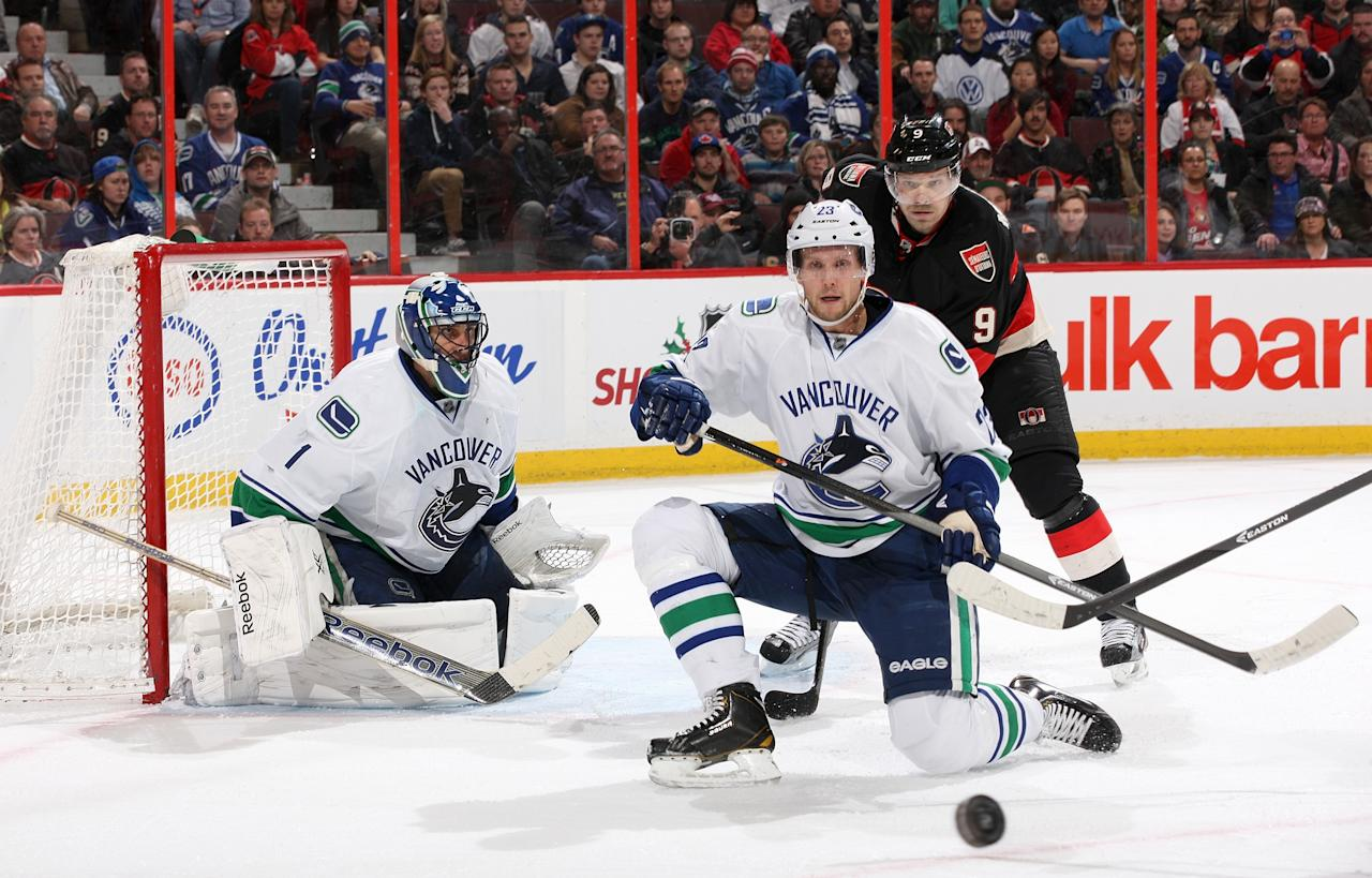 OTTAWA, ON - NOVEMBER 28: Alexander Edler #23 of the Vancouver Canucks goes down on now knee as he and team mate Roberto Luongo #1 defend against Milan Michalek #9 of the Ottawa Senators during an NHL game at Canadian Tire Centre on November 28, 2013 in Ottawa, Ontario, Canada. (Photo by Jana Chytilova/Freestyle Photography/Getty Images)
