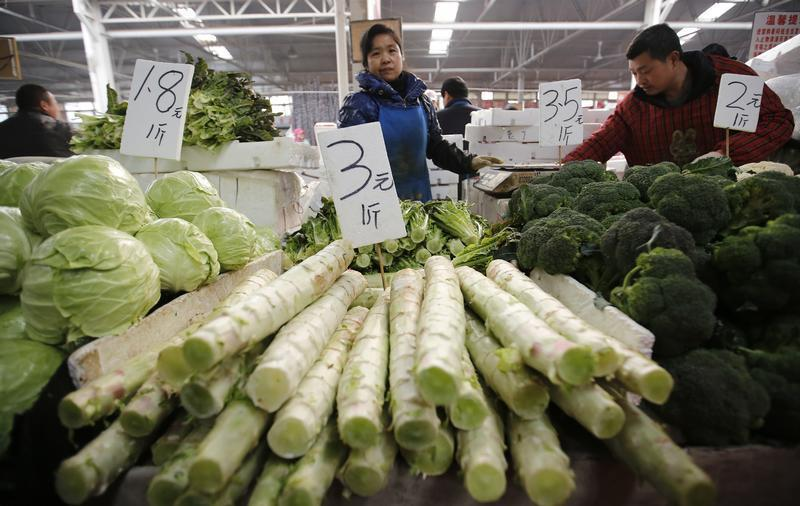 A vegetable vendor waits for customers at a market in Beijing
