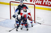 Russia's Kristi Shashkina, center, struggles to hold her position as Cayla Barnes, left, of the United States, checks her and goalie Alex Cavallini looks on during the second period of a match at the International Ice Hockey Federation (IIHF) Women's World Championships in Calgary, Alberta, Tuesday, Aug. 24, 2021. (Jeff McIntosh/The Canadian Press via AP)