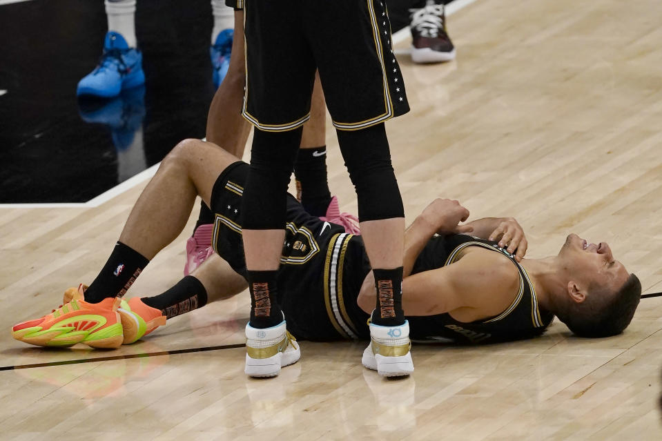 Atlanta Hawks guard Bogdan Bogdanovic (13) lies on the court after an injury during the first half of Game 6 of an NBA basketball Eastern Conference semifinal series against the Philadelphia 76ers, Friday, June 18, 2021, in Atlanta. Bogdanovic stayed in the game. (AP Photo/John Bazemore)
