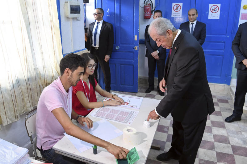 In this photo provided by the Tunisian Presidency, Tunisian President Mohamed Ennaceur inks his finger in a polling station during the first round of the presidential election, in Sidi Bou Said, north of Tunis, Tunisia, Sunday Sept. 15, 2019. Tunisians are casting ballots in their North African country's second democratic presidential election, choosing among 26 candidates for a leader who can safeguard its young democracy and tackle its unemployment, corruption and economic despair. (Slim Abid/Tunisian Presidency via AP)