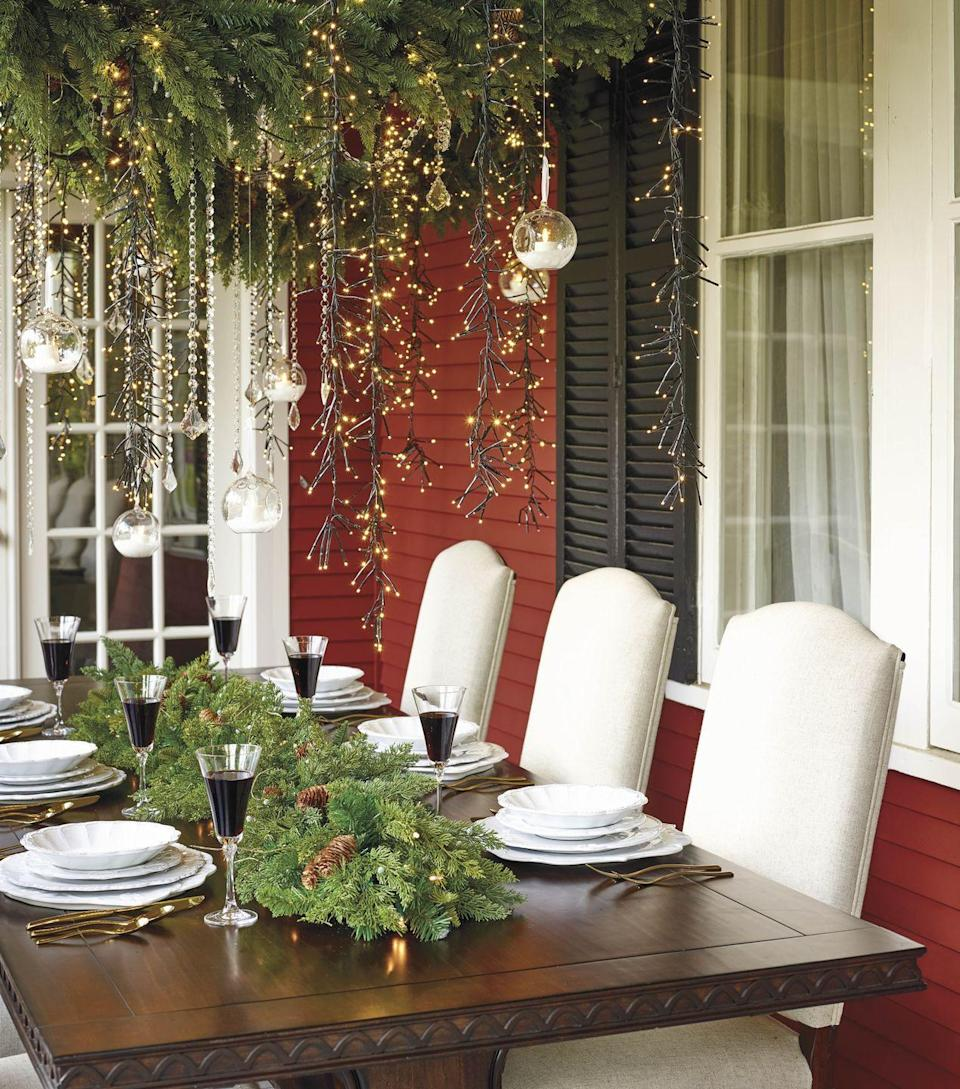 <p>For warm-weather holiday dwellers, dining outside for Christmas dinner is definitely a possibility. Create a luxurious hanging arrangement with wreaths, lights and candles.</p>
