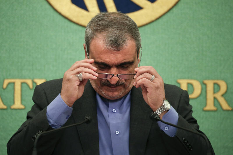 """Iranian Ambassador to Japan Morteza Rahmani Movahed puts on his reading glasses before speaking at a news conference Monday, June 24, 2019, in Tokyo. He said his country faces """"economic terrorism targeting Iranian people"""" as U.S. piles sanction after sanction on the country. (AP Photo/Jae C. Hong)"""
