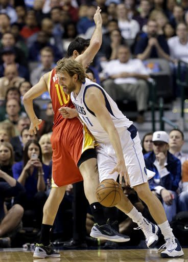Houston Rockets' Carlos Delfino (10), of Argentina, fouls Dallas Mavericks' Dirk Nowitzki (41), of Germany, as Nowitzki drives to the basket in the first half of an NBA basketball game, Wednesday, March 6, 2013, in Dallas. (AP Photo/Tony Gutierrez)