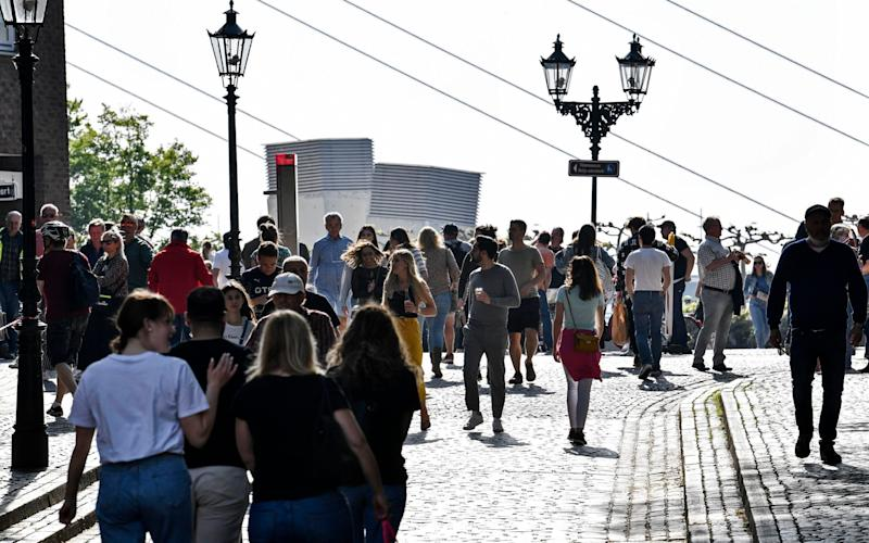 A lot of people enjoy the evening sun in the old town of Duesseldorf, Germany, despite the social distancing order to fight the coronavirus pandemic on Friday, April 24, 2020. (AP Photo/Martin Meissner) - Martin Meissner/AP