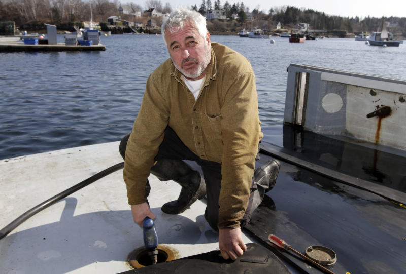 In this Tuesday, March 20, 2012 photo, third generation lobsterman Craig Rogers fuels up his lobster boat at Mackeral Cove in Bailey Island, Maine. Rogers, of Harpswell, said high fuel prices are the biggest concern of lobstermen today.(AP Photo/Pat Wellenbach)