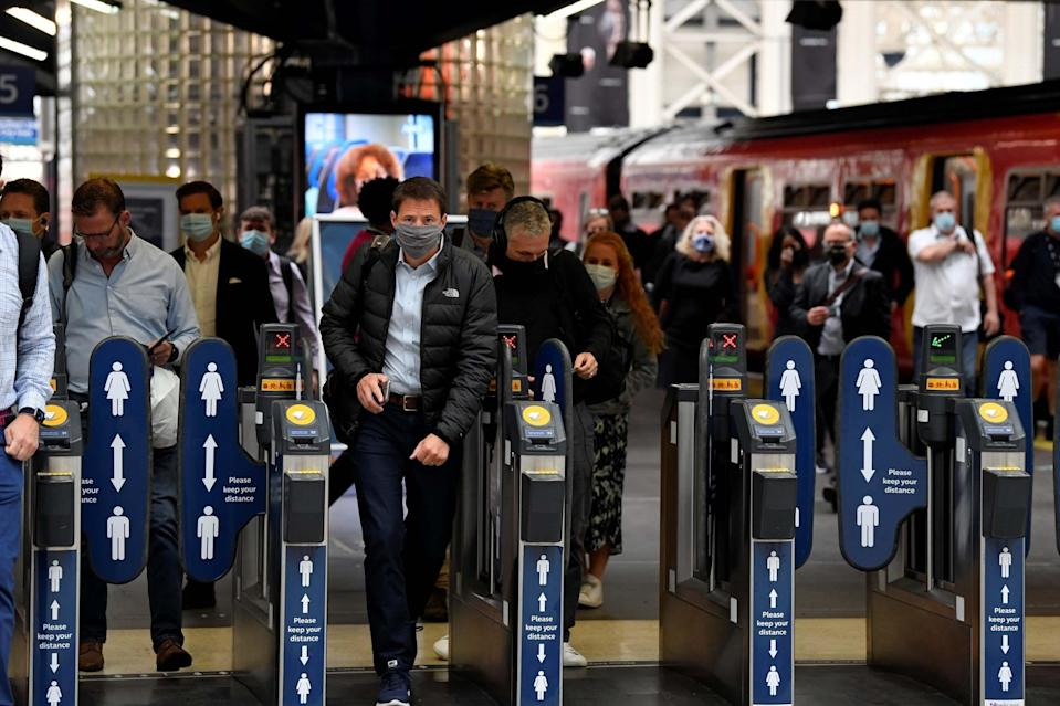 People wearing protective face masks are seen arriving at Waterloo station, the busiest train station in the UK: REUTERS