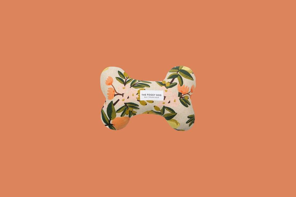 """<p>Treat your pup in style with this eco-friendly squeaky toy, handcrafted to be beautiful and durable—it features a pattern of lemons, oranges, and citrus blossoms designed by Rifle Paper Co. and screen-printed in Japan.</p> <p><strong><em>Shop Now: </em></strong><em>The Foggy Dog Valencia Natural Dog Squeaky Toy, $16, </em><a href=""""https://www.thefoggydog.com/collections/dog-toys/products/valencia-natural-dog-squeaky-toy"""" rel=""""nofollow noopener"""" target=""""_blank"""" data-ylk=""""slk:thefoggydog.com"""" class=""""link rapid-noclick-resp""""><em>thefoggydog.com</em></a><em>.</em></p>"""