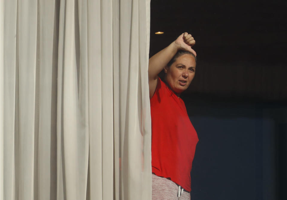 """A woman gestures towards the media from her room at the Radisson Blu Edwardian Hotel, near Heathrow Airport, London, Monday Feb. 15, 2021. Passengers from Heathrow airport they will remain at the hotel during a 10 day quarantine period after returning to England from one of 33 """"red list"""" countries. New regulations now in force require anyone who has been in a 'high-risk' location to enter England through a designated port and have pre-booked a package to stay at one of the Government's managed quarantine facilities. (AP Photo/Alastair Grant)"""